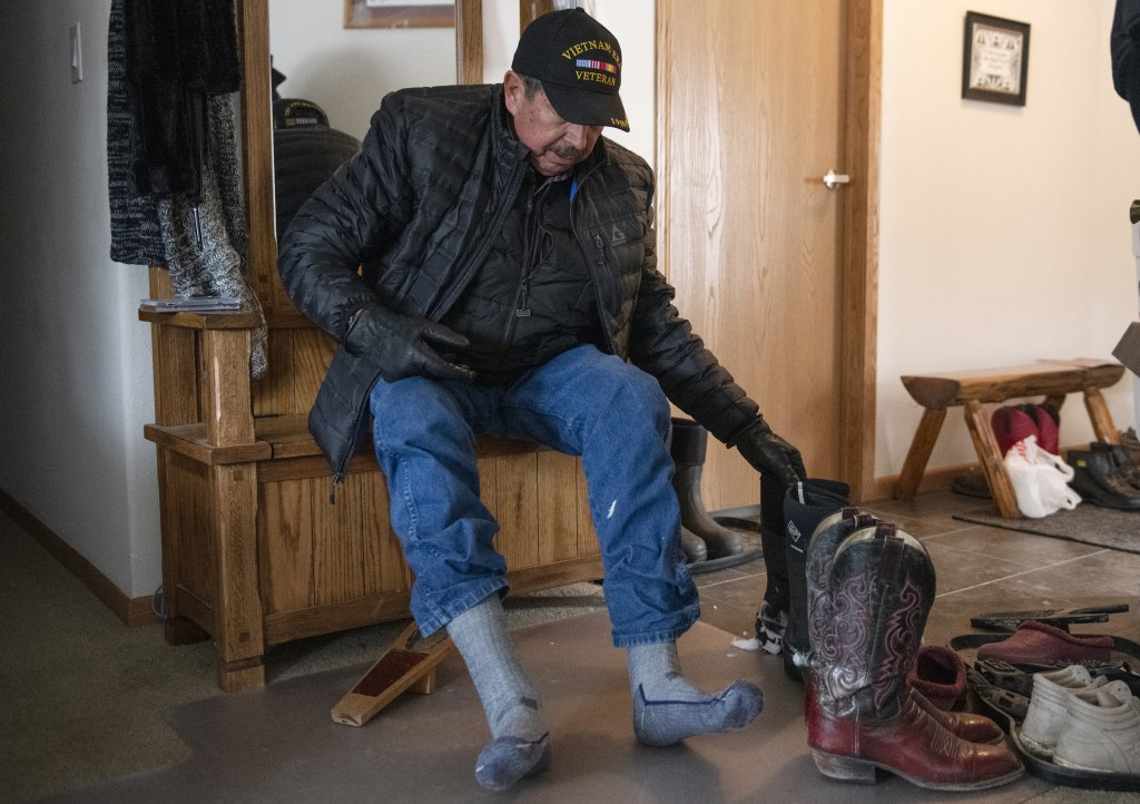 Richard King, 70, takes his boots off after shoveling his deck at his home on the King family ranch near Zortman, Mont., on Sunday, Dec. 8, 2019. King...