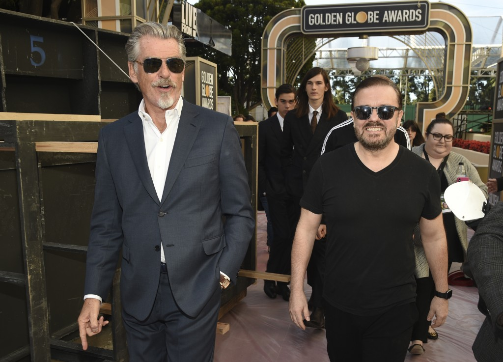 Ricky Gervais, right, host of Sunday's 77th Annual Golden Globe Awards, mingles with actor Pierce Brosnan during Preview Day for the Globes at the Bev...