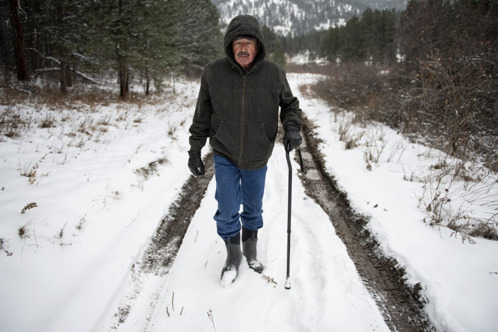 "Richard King, 70, walks down a muddy road on the family ranch near Zortman, Mont., on Sunday, Dec. 8, 2019. ""It's called complete serenity."" King said..."