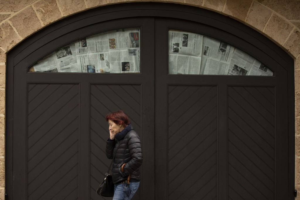 A woman talks on her mobile phone as she passes the house of ex-Nissan chief Carlos Ghosn, where windows are covered with newspaper to prevent journal...