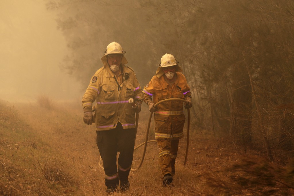 Firefighters drag their water hose after putting out a spot fire near Moruya, Australia, Saturday, Jan. 4, 2020. Australia's Prime Minister Scott Morr...