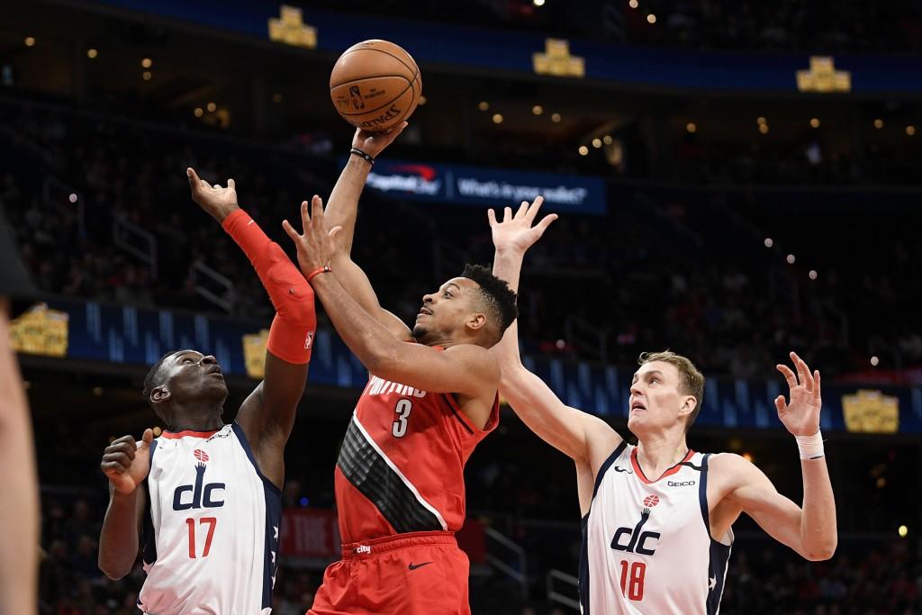 Portland Trail Blazers guard CJ McCollum (3) goes to the basket between Washington Wizards guard Isaac Bonga (17) and center Anzejs Pasecniks (18) dur...