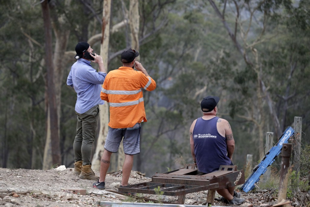 Residents on edge of Batemans Bay, Australia, relax after a fire threat near their homes eased Saturday, Jan. 4, 2020. Australia's prime minister call...