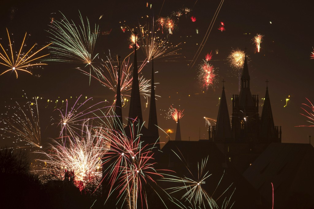 Fireworks light the sky above the St. Severi's Church, left, and the Mariendom (Cathedral of Mary), right, during New Year's celebrations in Erfurt, c...