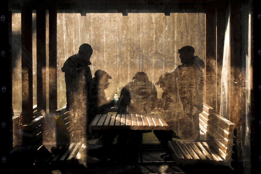 Men play chess, lit by the setting sun, while others watch in a park in Bucharest, Romania, Wednesday, Jan. 1, 2020. (AP Photo/Vadim Ghirda)