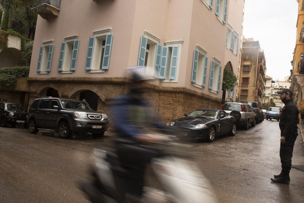 A motorbike passes a private security guard standing outside of the house of ex-Nissan chief Carlos Ghosn in Beirut, Lebanon, Saturday, Jan. 4, 2020. ...