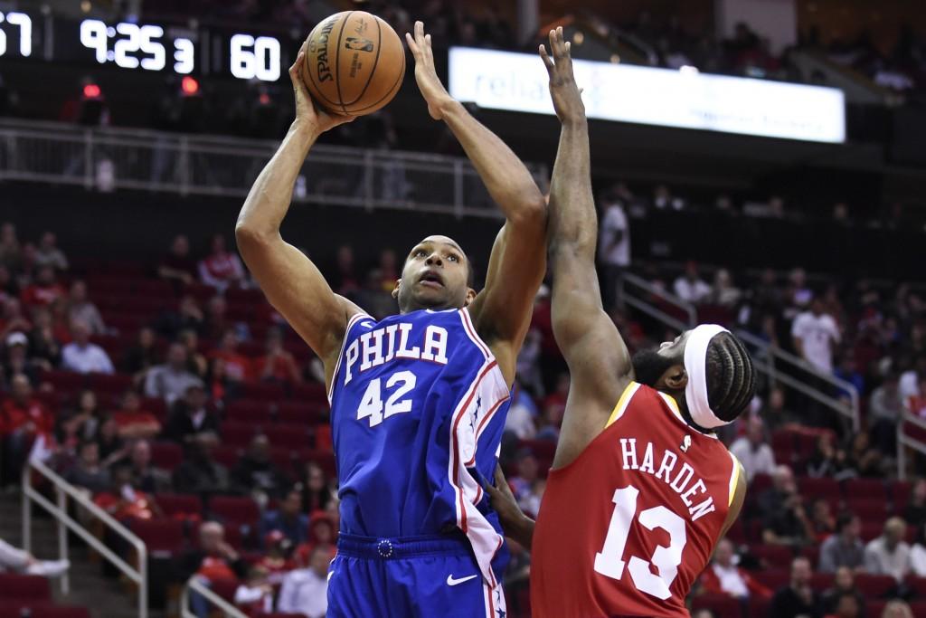 Philadelphia 76ers center Al Horford (42) shoots as Houston Rockets guard James Harden defends during the second half of an NBA basketball game, Frida...
