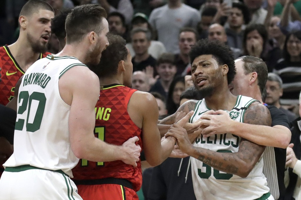 Boston Celtics guard Marcus Smart, right, is held back by a referee as Celtics forward Gordon Hayward (20) holds Atlanta Hawks guard Trae Young (11) d...