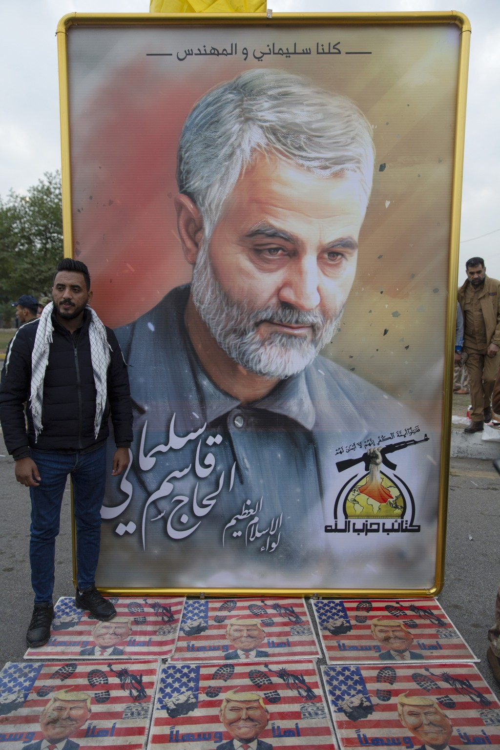 """Mourners step over a U.S. flags with pictures of U.S. President Donald Trump, under a picture of Qasem Soleimani with Arabic that reads """"We are all So..."""