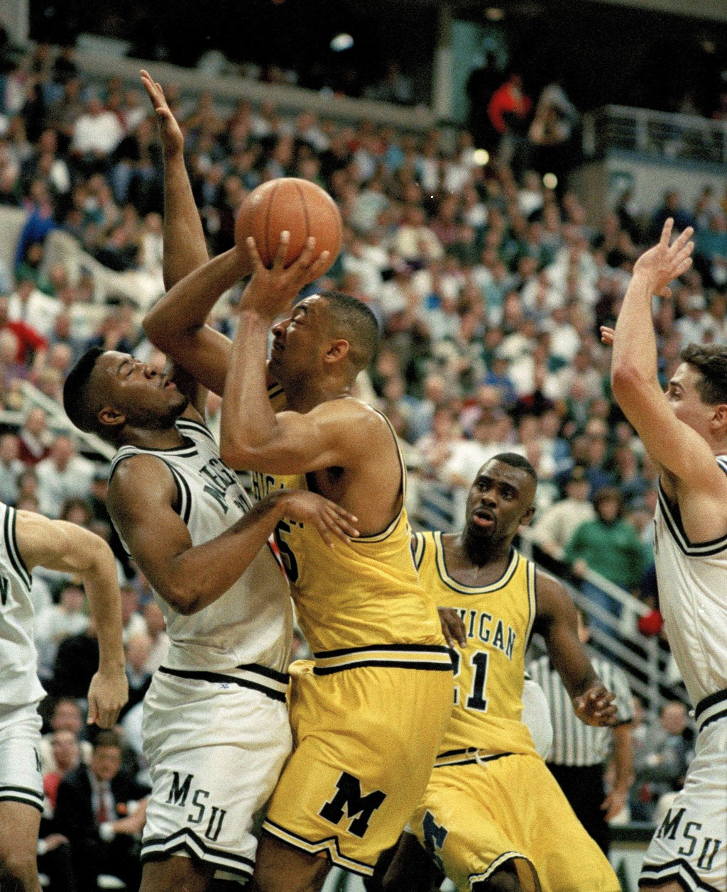 FILE - In this Feb. 3, 1993 file photo, Michigan's Juwan Howard, right, pushes against Michigan State's Dwayne Stephens as he goes up for a shot durin...