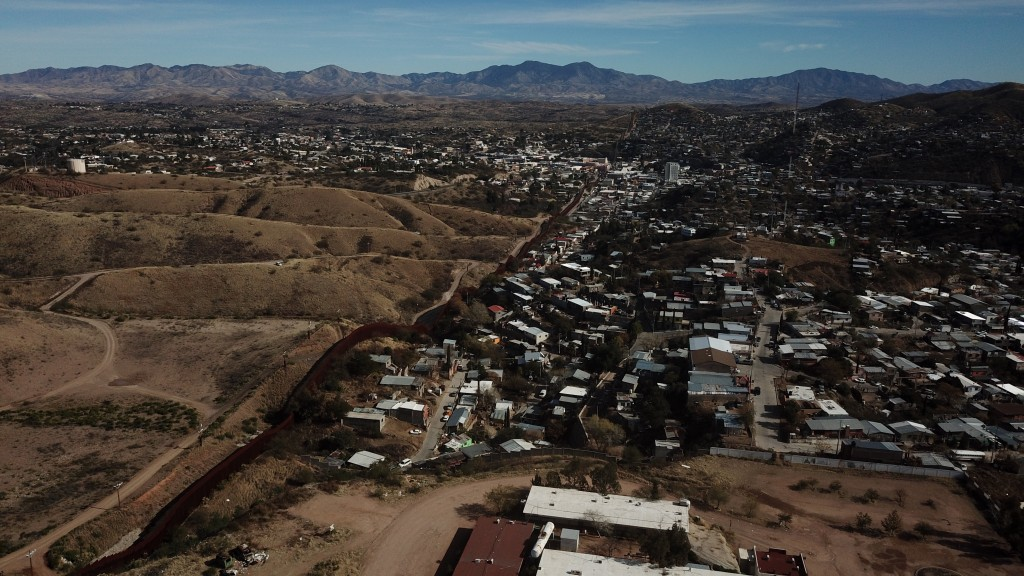 The U.S. border fence separates Nogales, Mexico, right, from sister city Nogales, Arizona, left, Friday, Jan. 3, 2020. Dozens of asylum seekers pushed...