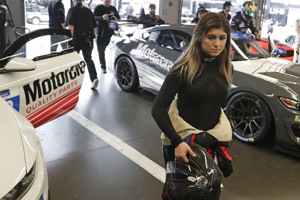 Hailie Deegan walks through her garage before the start of a practice session during testing for the upcoming Rolex 24 hour auto race at Daytona Inter...