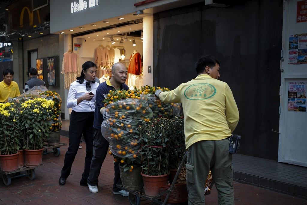Workers push carts loaded with mandarin orange plants and flowers to their customer passing by a closed shop lot covered with steel panel in Hong Kong...