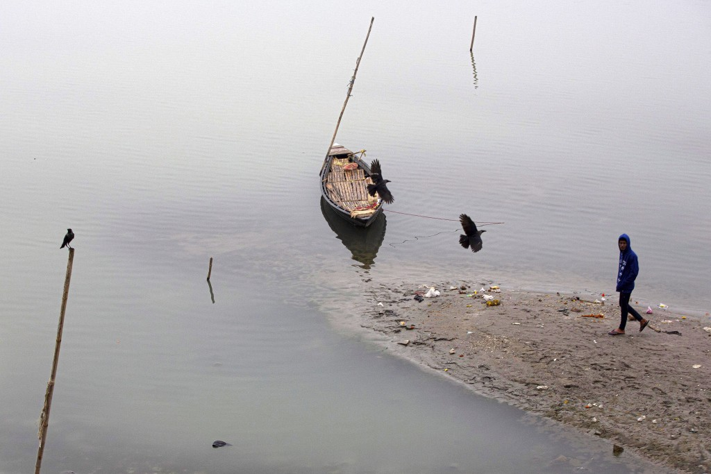 Birds fly over an anchored boat in the river Brahmaputra on a cold winter morning in Gauhati, India, Friday, Jan. 3, 2020. Brahmaputra is one of Asia'...