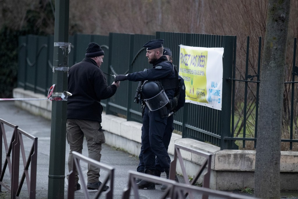 A riot police officer checks a badge after a man attacked passerby Friday Jan.3, 2020 in Villejuif, south of Paris. A man armed with a knife rampaged ...