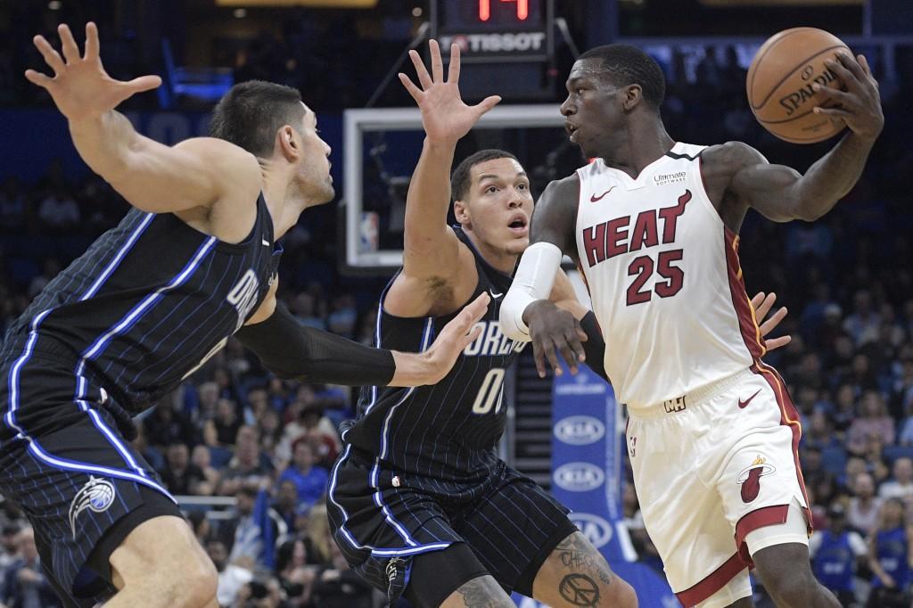 Miami Heat guard Kendrick Nunn (25) looks to pass the ball in front of Orlando Magic center Nikola Vucevic (9), left, and forward Aaron Gordon (00) du...