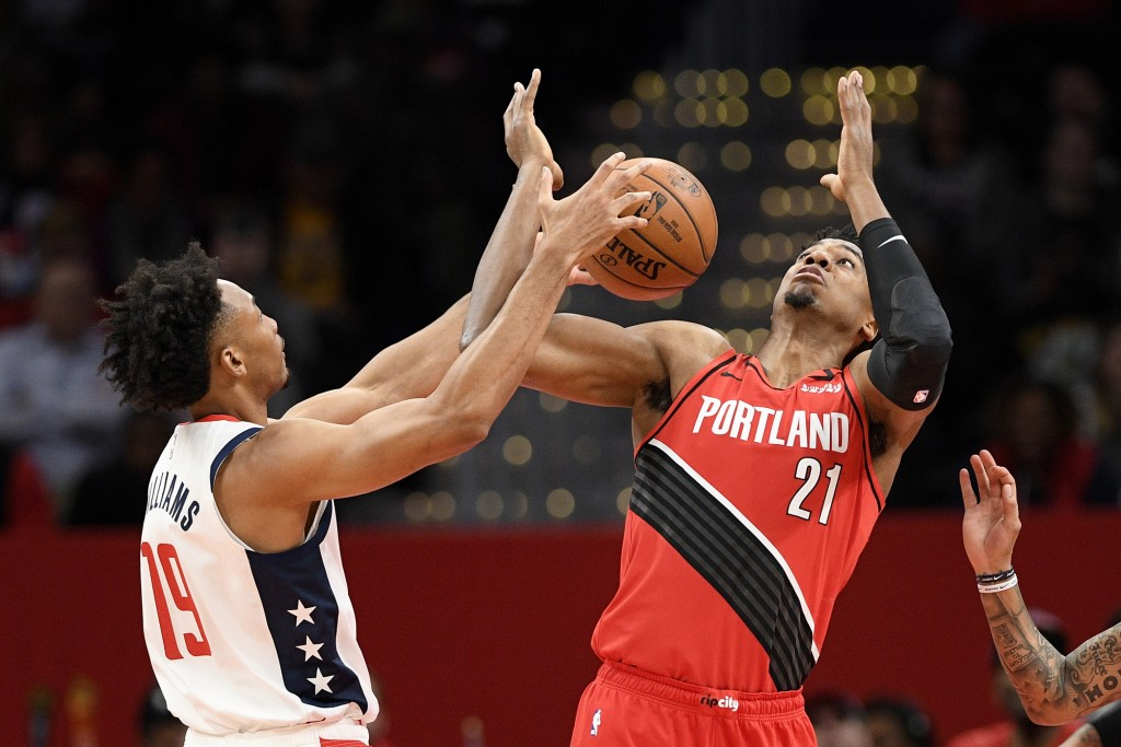 Portland Trail Blazers center Hassan Whiteside (21) and Washington Wizards forward Johnathan Williams (19) battle for the ball during the first half o...