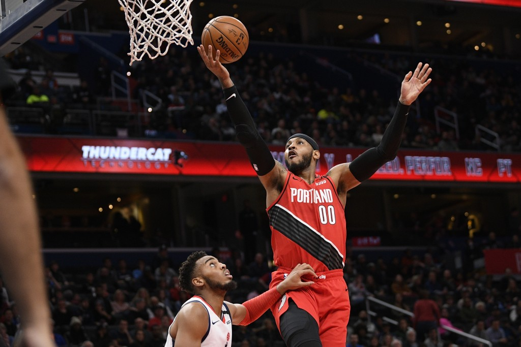 Portland Trail Blazers forward Carmelo Anthony (00) goes to the basket next to Washington Wizards guard Troy Brown Jr., left, during the first half of...