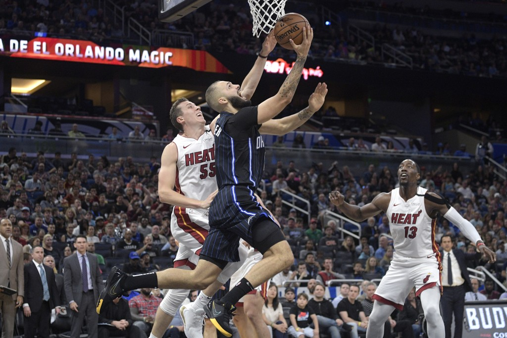 Orlando Magic guard Evan Fournier goes up to shoot in front of Miami Heat forward Duncan Robinson (55) as center Bam Adebayo (13) watches during the s...