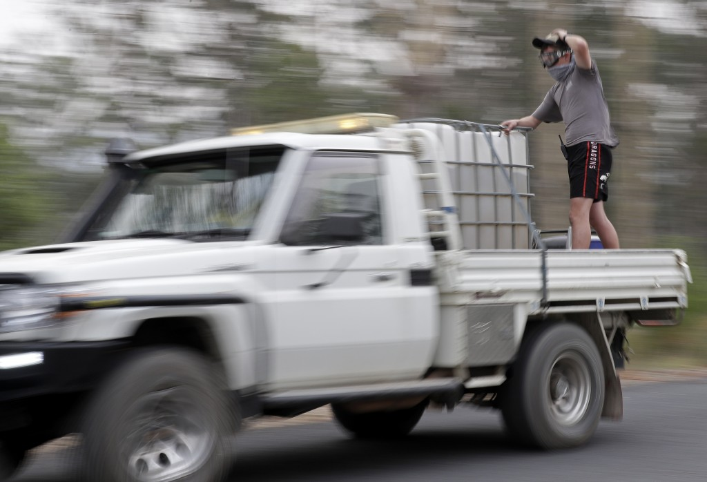 A man stands in the back of a truck as they patrol a fire at Batemans Bay, Australia, Saturday, Jan. 4, 2020. Australia's prime minister called up abo...