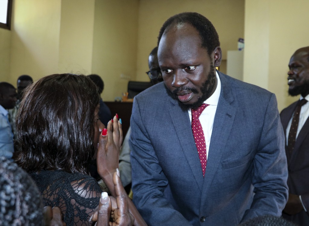 FILE - In this Tuesday, June 11, 2019 file photo, prominent South Sudanese activist and economist Peter Biar Ajak prepares to embrace his wife Nyathon...