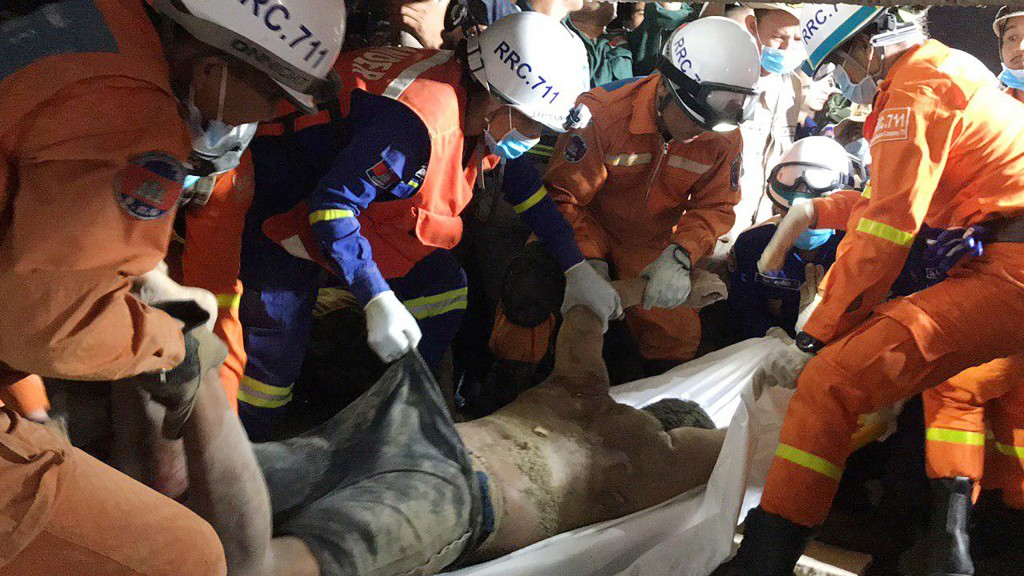 In this photo provided by the Kep Provincial Authority, emergency workers remove the body of a victim from a collapsed building in Kep province, south...