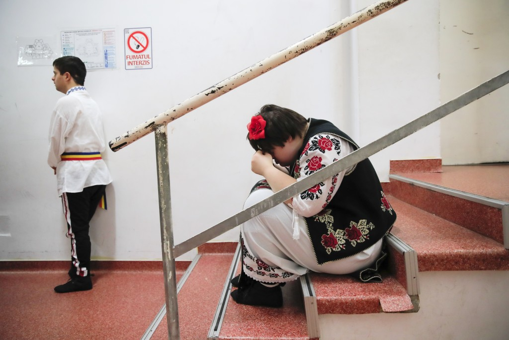 In this Dec. 3, 2019, photograph a girl with Down syndrome wipes her eyes before performing in a dance show, in Bucharest, Romania. Children with Down...