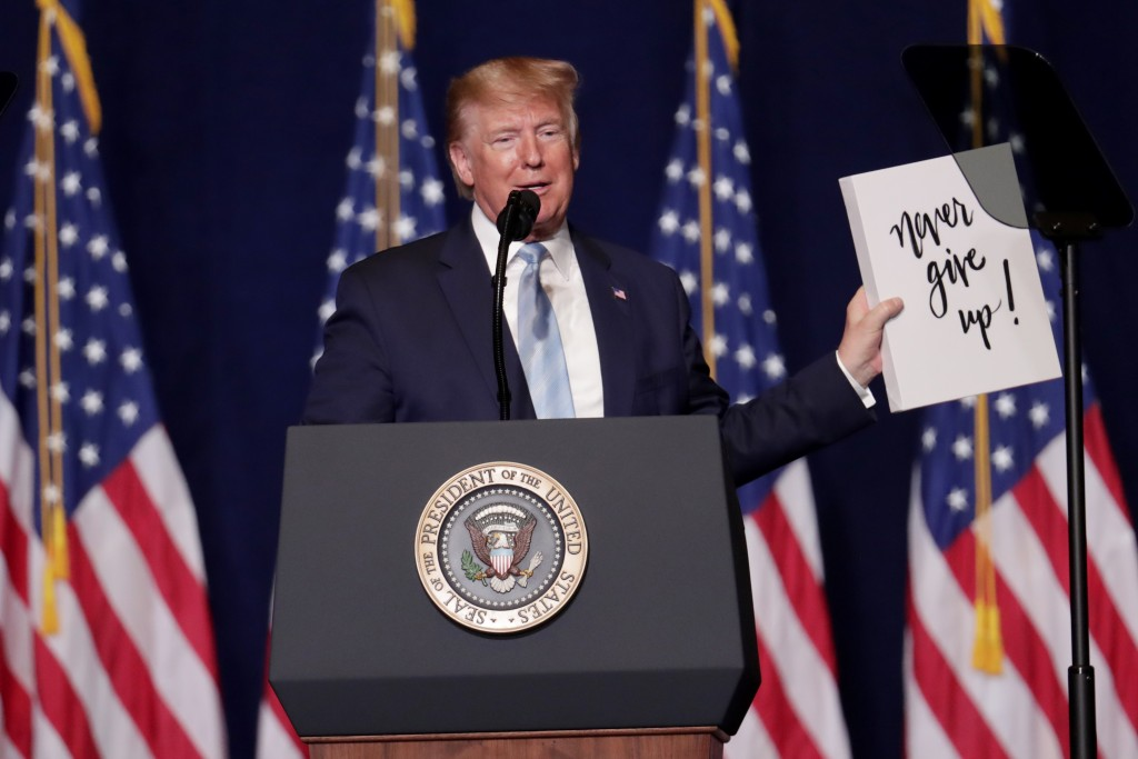 President Donald Trump holds up a sign given to him by a supporter during a rally for evangelical supporters at the King Jesus International Ministry,...