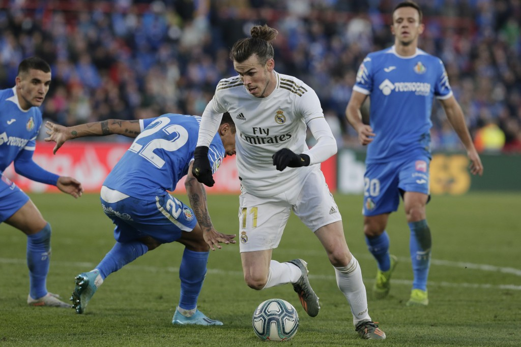 Real Madrid's Gareth Bale, center, dribbles through the defence during a Spanish La Liga soccer match between Getafe and Real Madrid at the Coliseum A...