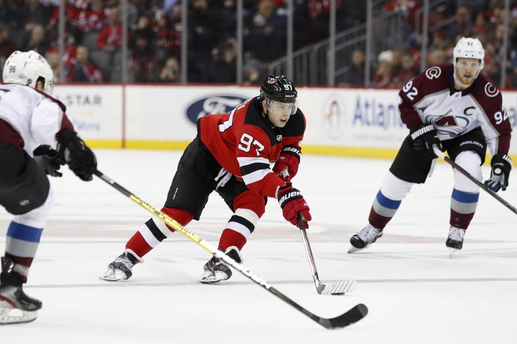 New Jersey Devils left wing Nikita Gusev (97), of Russia, skates between Colorado Avalanche right wing Mikko Rantanen (96), of Finland, and left wing ...