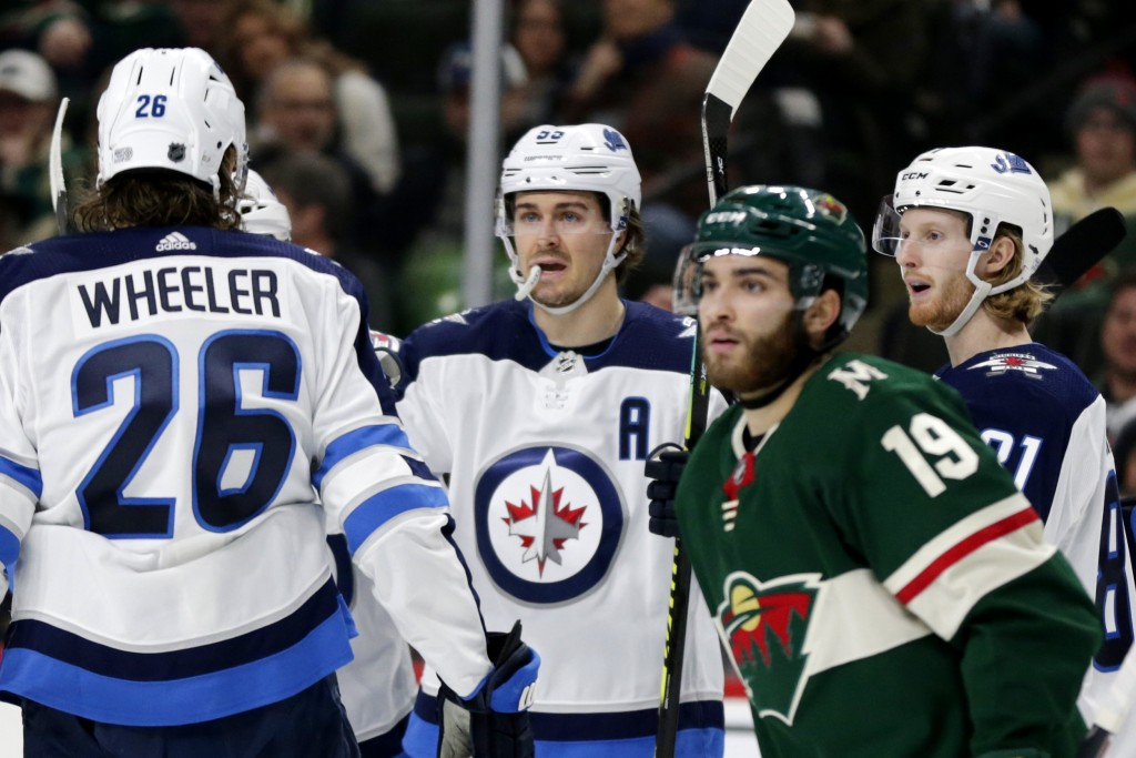 Winnipeg Jets center Mark Scheifele (55) is congratulated by teammates Jets' Blake Wheeler (26) and Jets' Kyle Connor (21) after scoring a goal as Min...