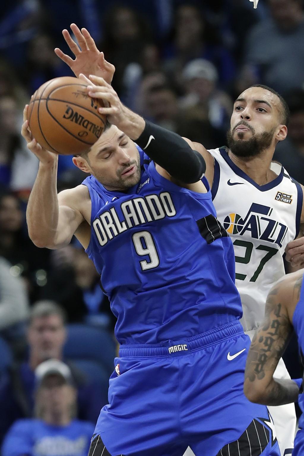 Orlando Magic center Nikola Vucevic (9) grabs a rebound in front of Utah Jazz center Rudy Gobert (27) during the first half of an NBA basketball game,...