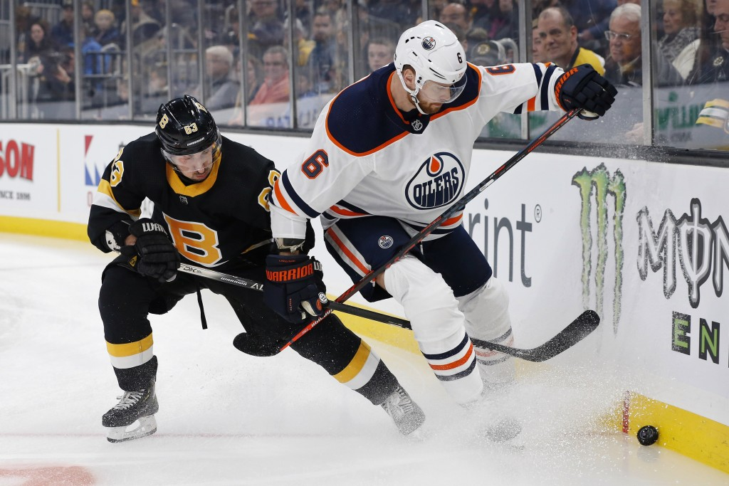 Boston Bruins' Brad Marchand (63) battles Edmonton Oilers' Adam Larsson (6) for the puck during the first period on an NHL hockey game in Boston, Satu...
