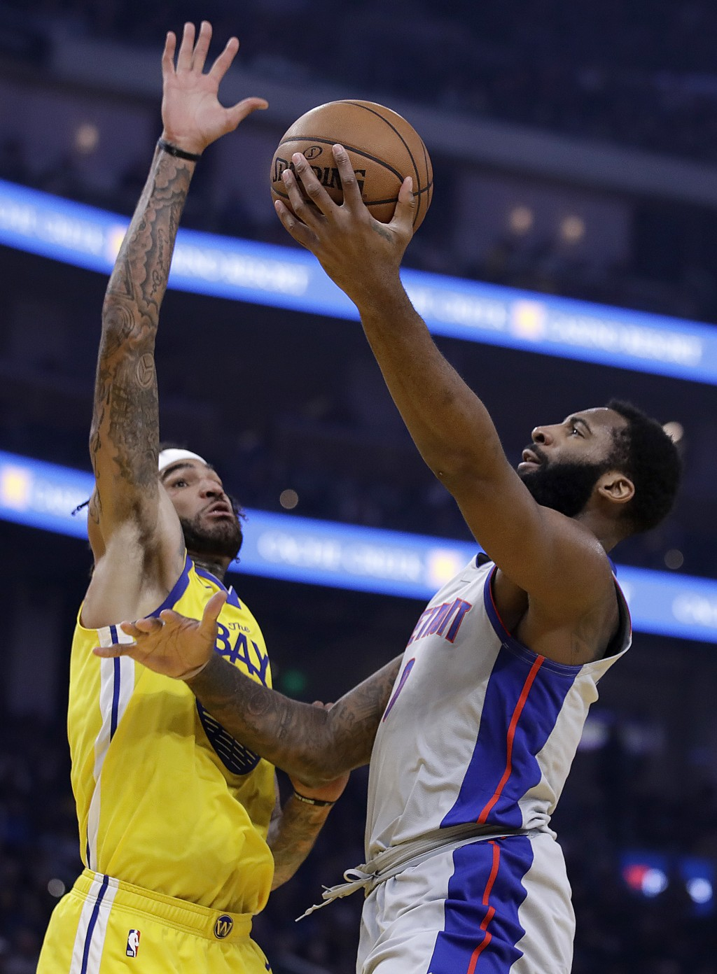 Detroit Pistons' Andre Drummond, right, lays up a shot against Golden State Warriors' Willie Cauley-Stein during the first half of an NBA basketball g...