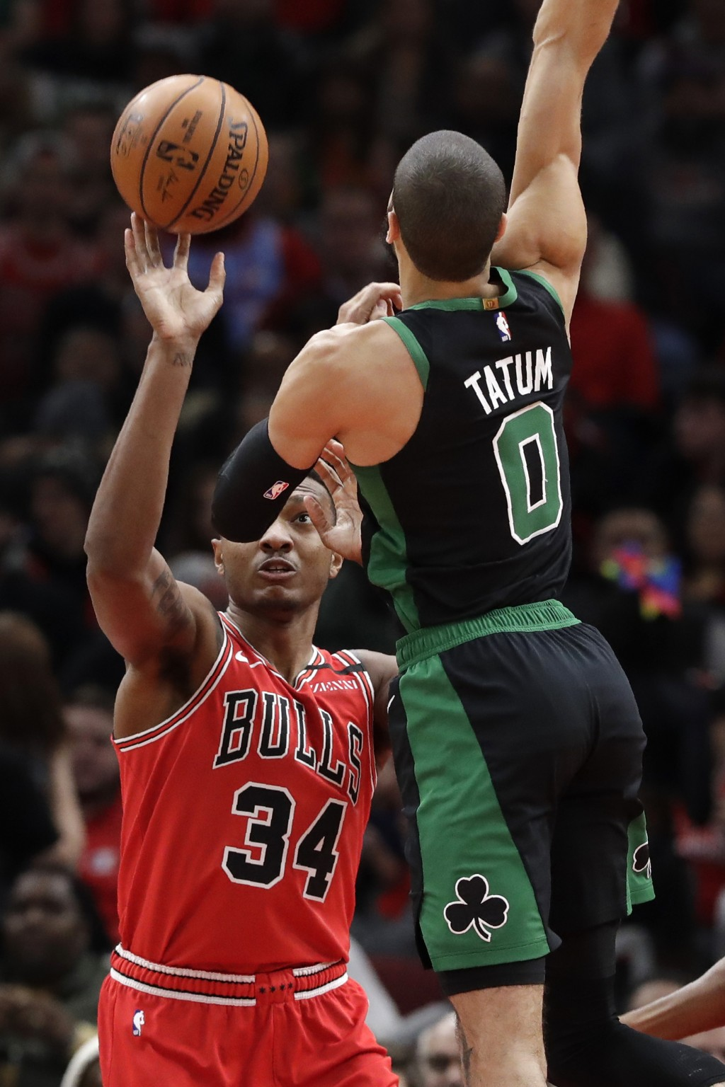 Chicago Bulls center Wendell Carter Jr., left, is defended by Boston Celtics forward Jayson Tatum during the first half of an NBA basketball game in C...