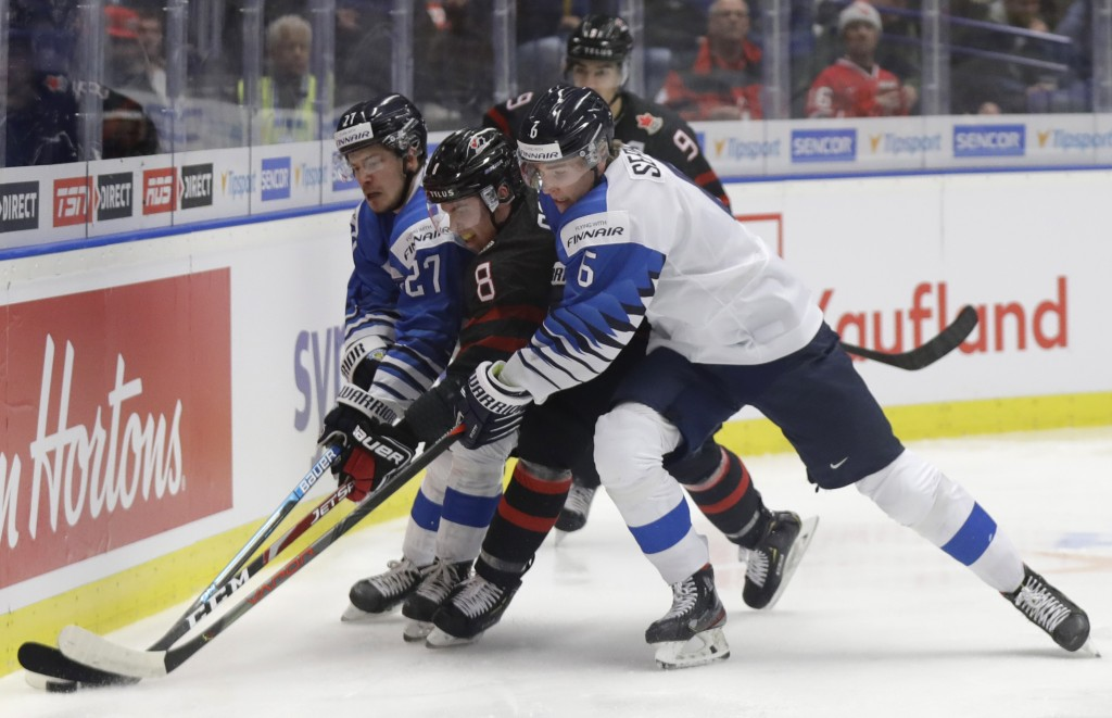 Finland's Kristian Tanus, left, and Finland's Peetro Seppala, right, challenge Canada's Liam Foudy, center, during the U20 Ice Hockey Worlds semifinal...