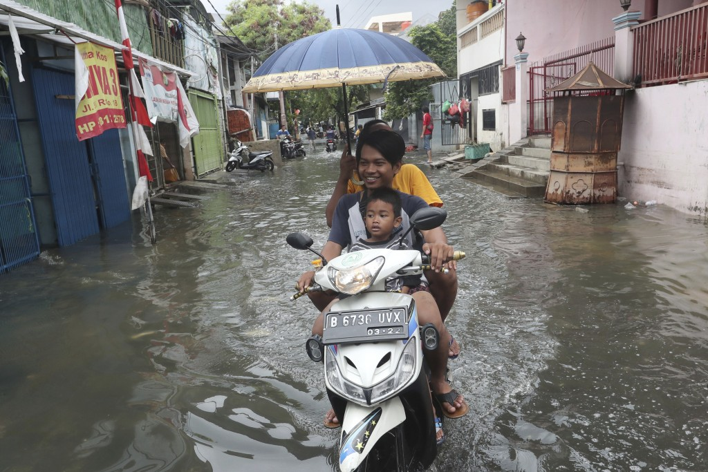 Residents ride a motorbike on a flooded street in Jakarta, Indonesia, Sunday, Jan. 5, 2020. Landslides and floods triggered by torrential downpours ha...