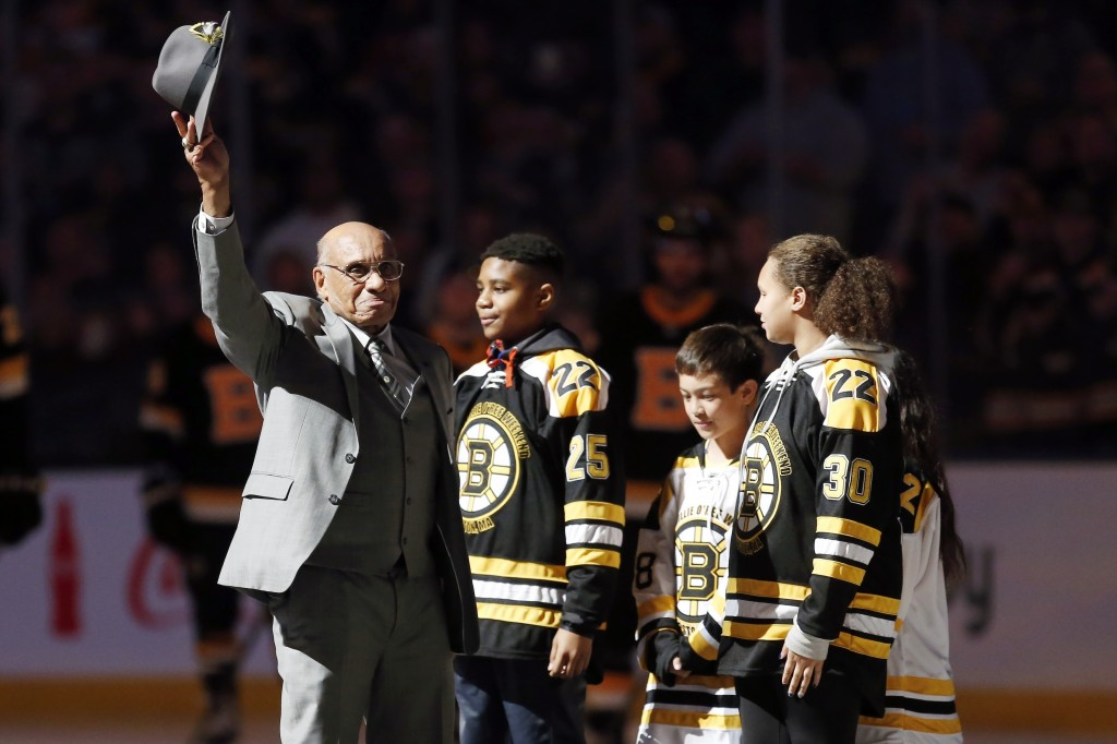 Hockey Hall of Famer Willie O'Ree, right, waves to the crowd before dropping the ceremonial puck before an NHL hockey game between the Boston Bruins a...