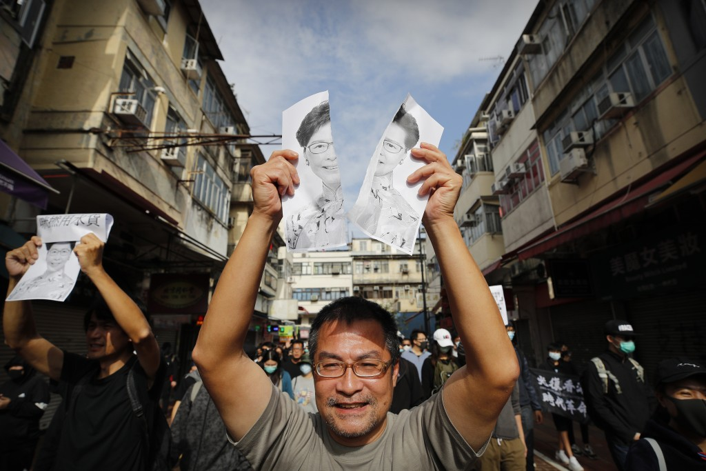 "A protester holds up a torn photo of Hong Kong Chief Executive Carrie Lam as he marches during a demonstration against ""parallel traders"" who buy good..."