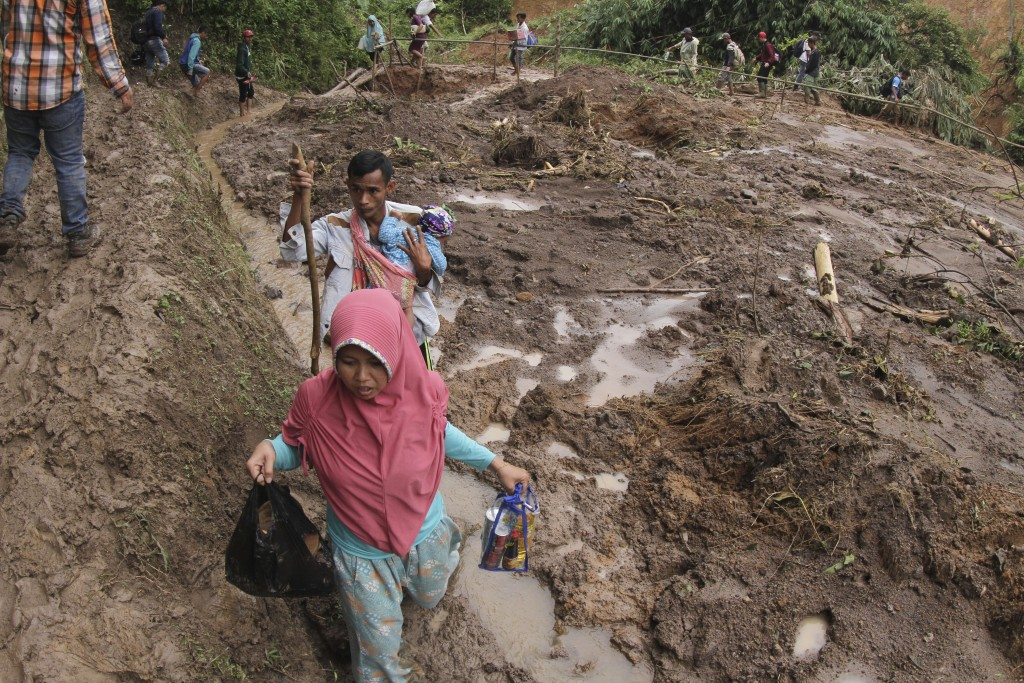 Villagers make their way at an area affected by a landslide in Sukajaya, West Java, Indonesia, Sunday, Jan. 5, 2020. Landslides and floods triggered b...
