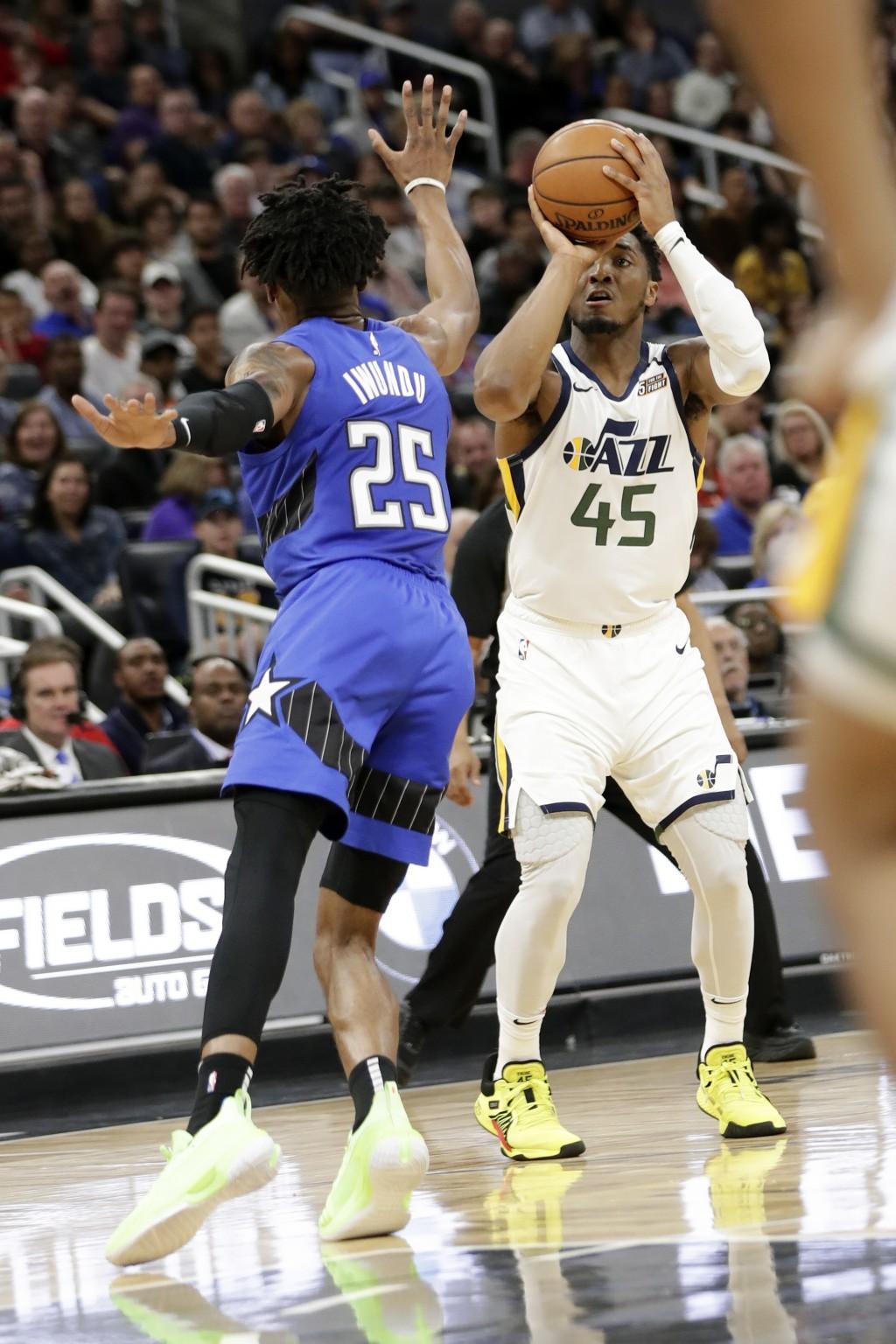 Utah Jazz guard Donovan Mitchell (45) takes a shot over Orlando Magic forward Wes Iwundu (25) during the second half of an NBA basketball game, Saturd...