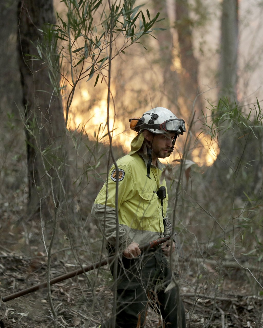 A firefighter keeps an eye on a controlled burn used to control a larger fire near Burrill Lake, Australia, Sunday, Jan. 5, 2020. Milder temperatures ...