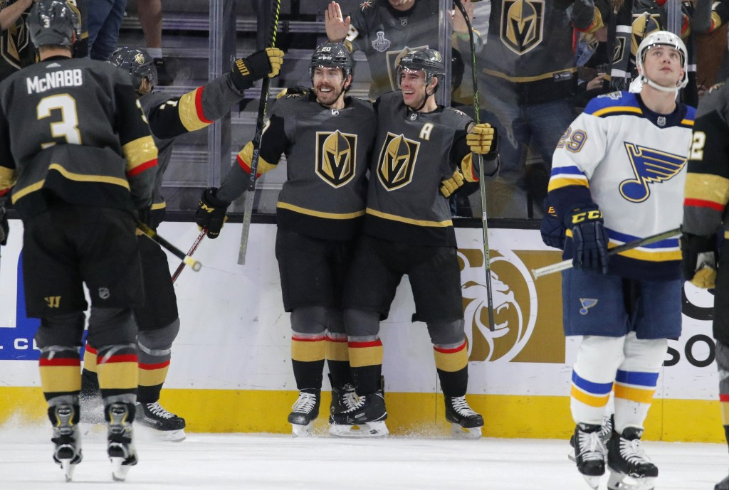 Vegas Golden Knights center Chandler Stephenson, center left, celebrates after right wing Reilly Smith, center right, scored against the St. Louis Blu...