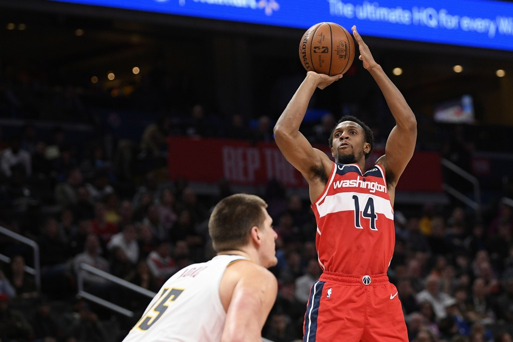 Washington Wizards guard Ish Smith (14) shoots in front of Denver Nuggets center Nikola Jokic (15) during the second half of an NBA basketball game, S...