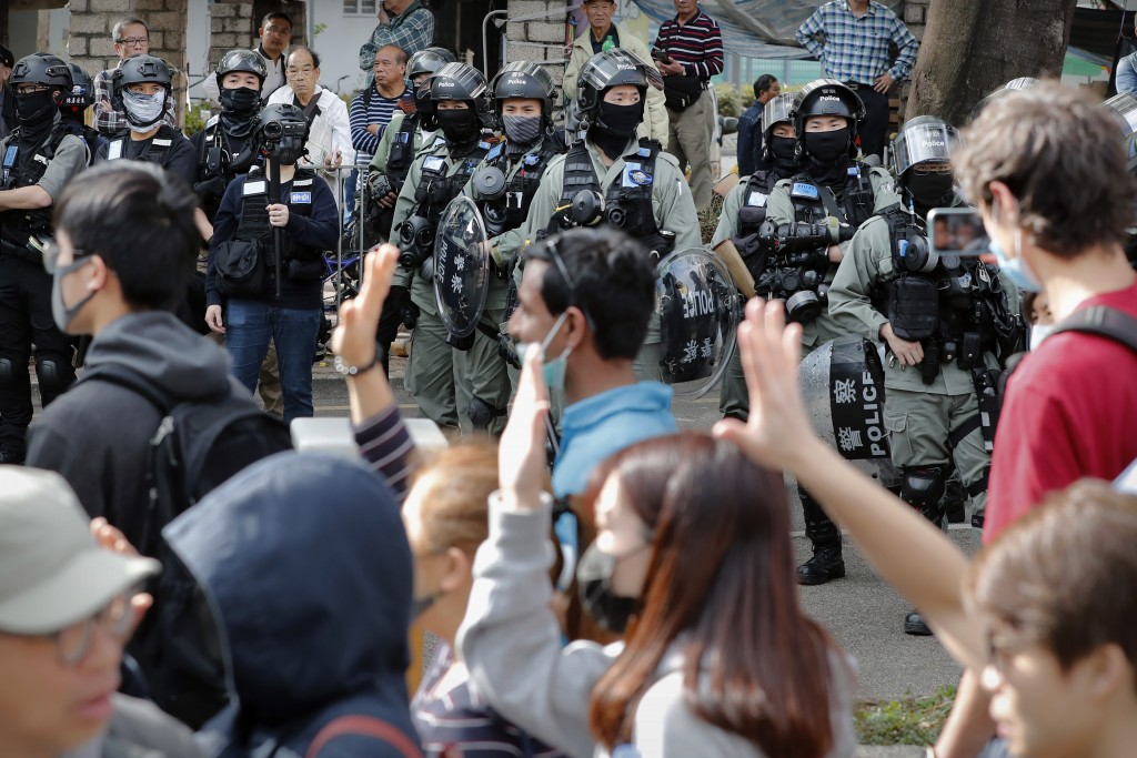 "Riot police watch as protesters march during a demonstration against ""parallel traders"" who buy goods in Hong Kong to resell in mainland China in Sheu..."