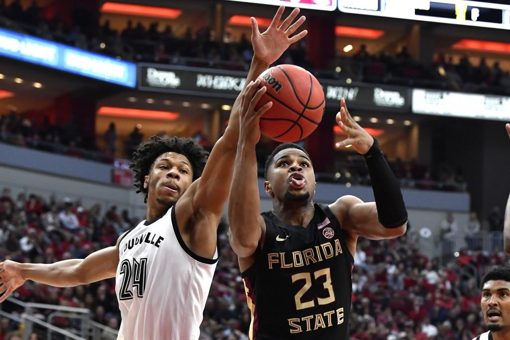 Florida State guard M.J. Walker (23) attempts to shoot past the defense of Louisville forward Dwayne Sutton (24) during the first half of an NCAA coll...