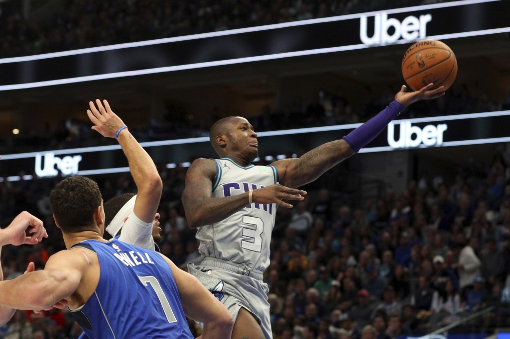 Charlotte Hornets guard Terry Rozier (3) shoots past Dallas Mavericks forward Dwight Powell (7) in the first half in an NBA basketball game Saturday, ...