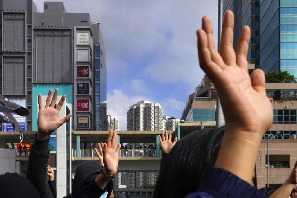 "Protesters raise their hands to symbolize the five demands of the pro-democracy movement during a demonstration against ""parallel traders"" who buy goo..."