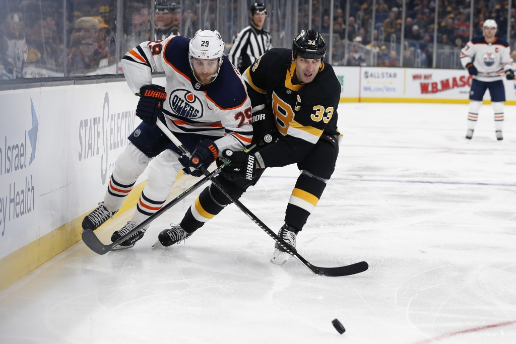 Edmonton Oilers' Leon Draisaitl (29) ad Boston Bruins' Zdeno Chara (33) battle for the puck during the second period on an NHL hockey game in Boston, ...