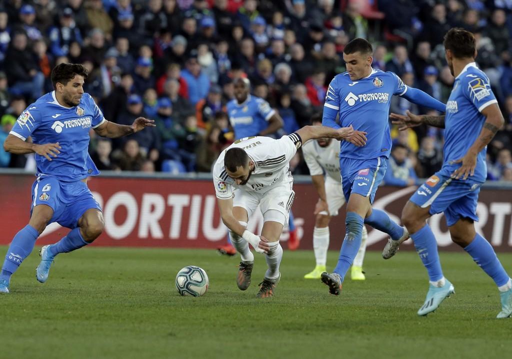Real Madrid's Karim Benzema, center, falls during a Spanish La Liga soccer match between Getafe and Real Madrid at the Coliseum Alfonso Perez stadium ...